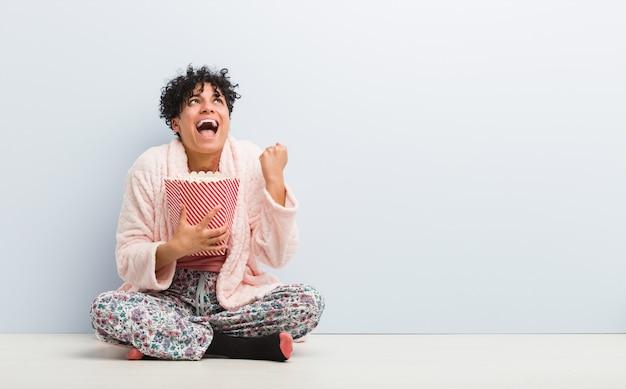 Giovane donna afroamericana che tiene un secchio del popcorn che incoraggia spensierato ed eccitato. concetto di vittoria.
