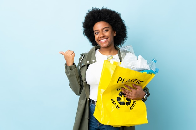 Giovane donna afroamericana che tiene una borsa di riciclaggio isolata sull'indicare variopinto al lato per presentare un prodotto