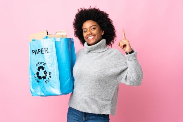 Giovane donna afroamericana che tiene una borsa di riciclaggio isolata sulla parete variopinta che indica su una grande idea