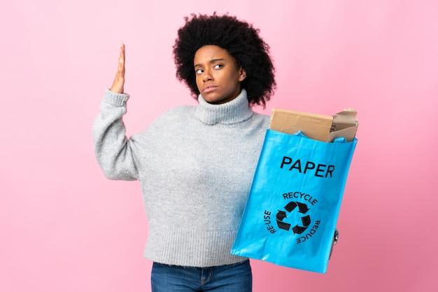 Giovane donna afroamericana che tiene una borsa di riciclaggio sulla parete colorata con espressione stanca e malata