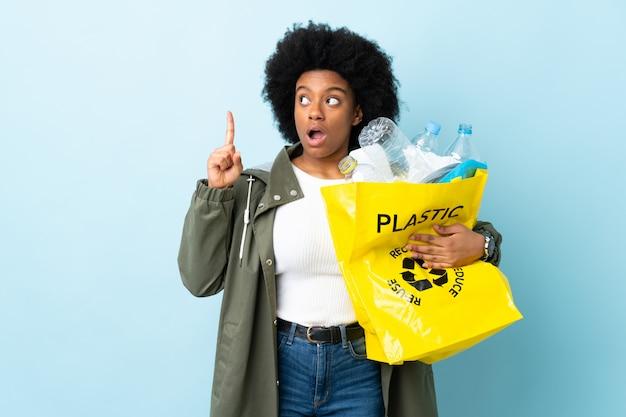 Giovane donna afroamericana che tiene una borsa di riciclaggio sulla parete variopinta che pensa un'idea che indica il dito su