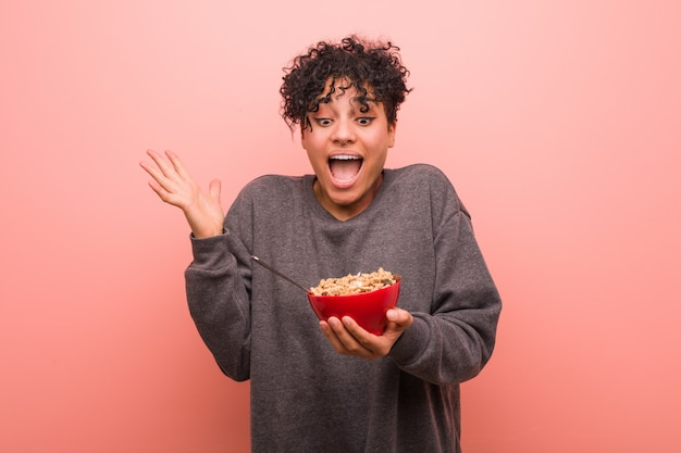 Giovane donna afroamericana che tiene una ciotola di cereali che celebra una vittoria o un successo