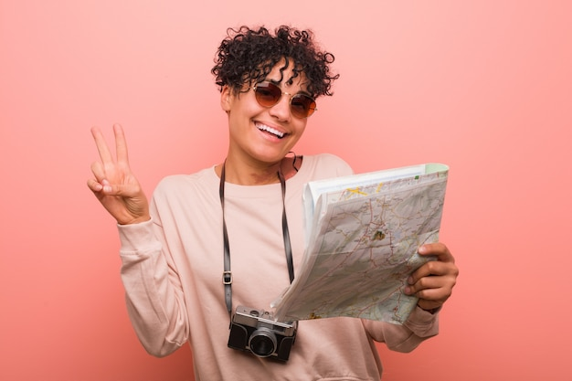 Giovane donna afroamericana che tiene una mappa che mostra numero due con le dita.