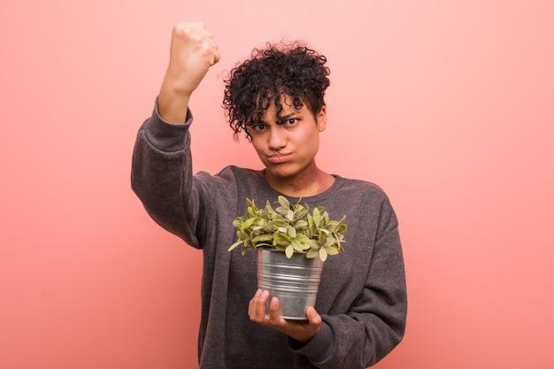 Giovane donna afroamericana che tiene una pianta che mostra numero uno con il dito.