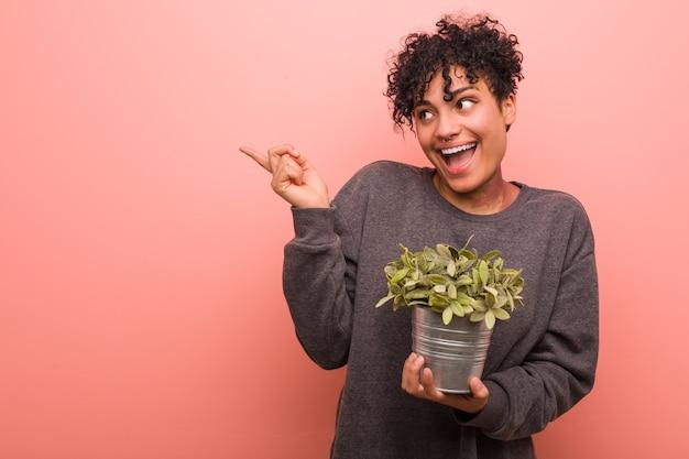 Giovane donna afroamericana che tiene una pianta che sorride allegramente indicando con l'indice di distanza.