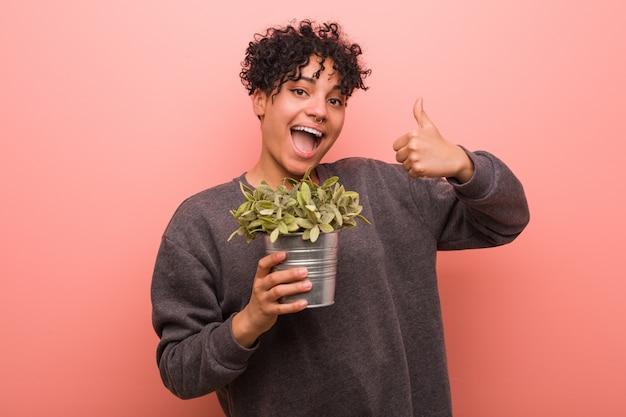 Giovane donna afroamericana che tiene una pianta che sorride e che alza pollice in su