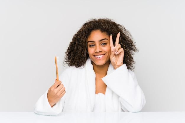 Giovane donna afroamericana che tiene uno spazzolino da denti che mostra il segno di vittoria e che sorride ampiamente.