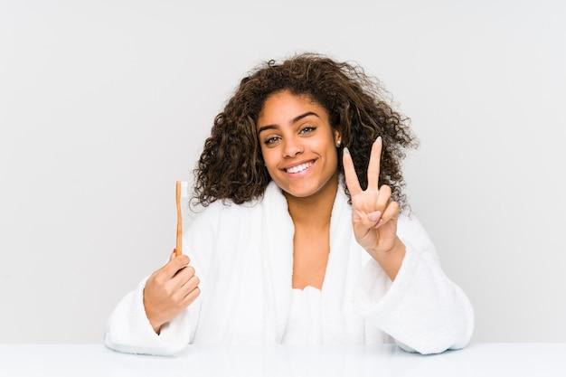 Giovane donna afroamericana che tiene uno spazzolino da denti che mostra numero due con le dita.