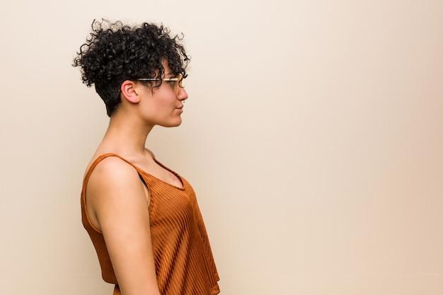 Giovane donna afroamericana con il segno di nascita della pelle che guarda a sinistra, posa laterale.