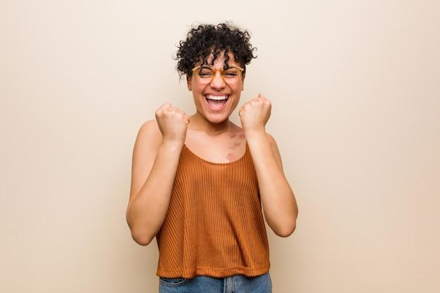 Giovane donna afroamericana con il segno di nascita della pelle che incoraggia spensierato ed eccitato. concetto di vittoria.
