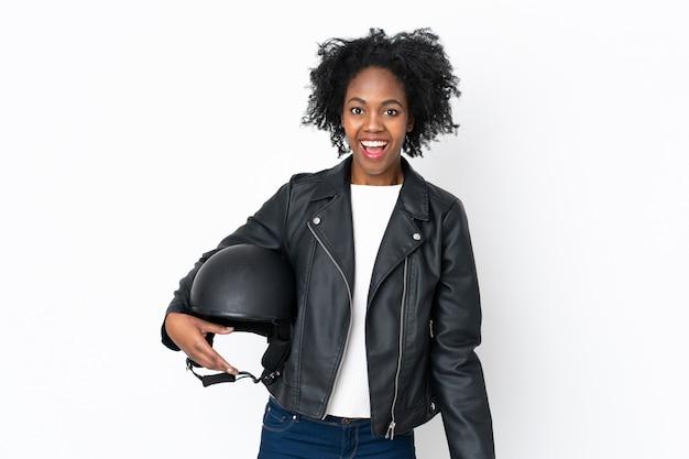 Giovane donna afroamericana con un casco del motociclo isolato su bianco