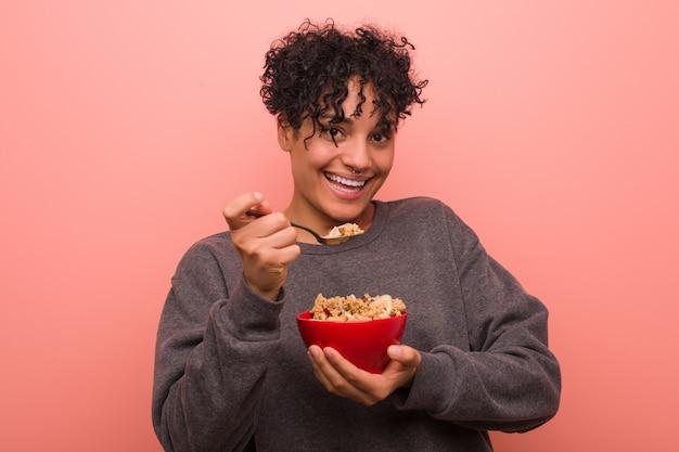Giovane donna afroamericana con una voglia in possesso di una ciotola di cereali