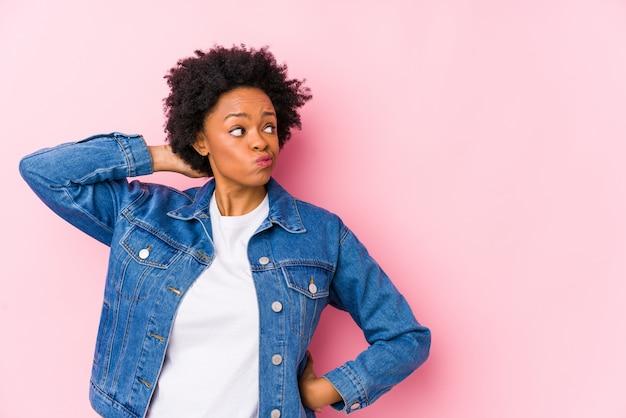 Giovane donna afroamericana contro una parete rosa che tocca la parte posteriore della testa, pensando e facendo una scelta.
