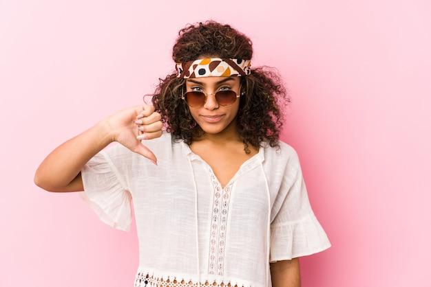 Giovane donna afroamericana dei pantaloni a vita bassa isolata sulla parete rosa che mostra un gesto di avversione, pollici giù. concetto di disaccordo.