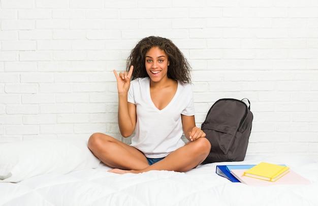 Giovane donna afroamericana dello studente sul letto che mostra un gesto dei corni come concetto di rivoluzione.