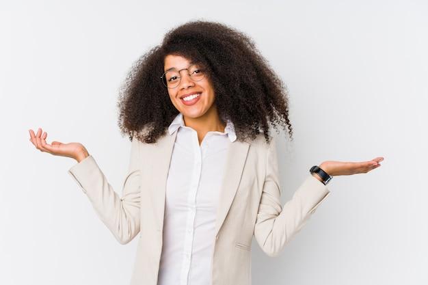 Giovane donna afroamericana di affari che dubita e che scrolla le spalle le spalle nel gesto interrogante.