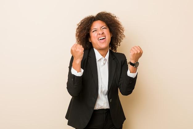 Giovane donna afroamericana di affari che incoraggia spensierata ed eccitata. concetto di vittoria.