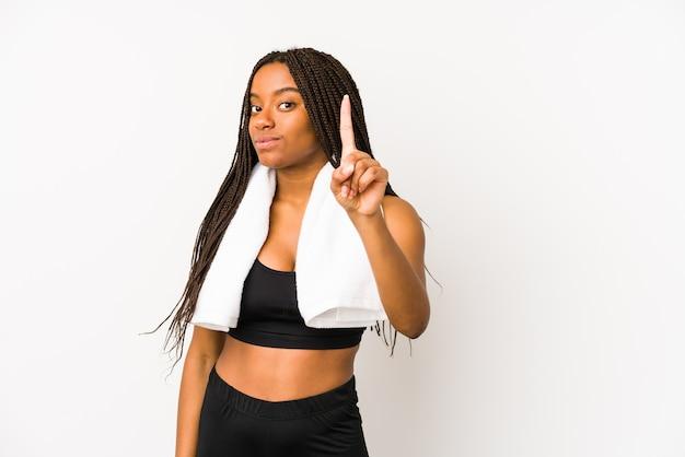Giovane donna afroamericana di sport isolata che mostra il numero uno con il dito.