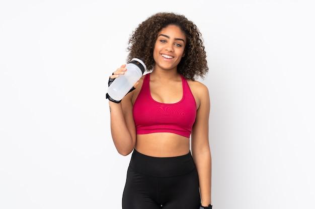 Giovane donna afroamericana di sport isolata su bianco con la bottiglia di acqua di sport