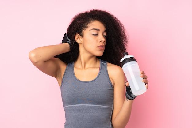 Giovane donna afroamericana di sport isolata sul rosa con la bottiglia di acqua di sport