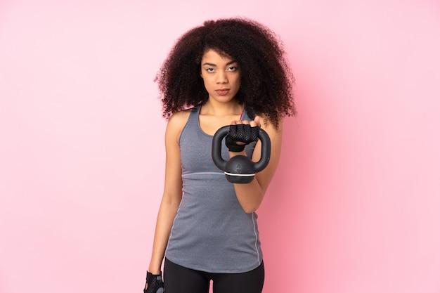 Giovane donna afroamericana di sport isolata sul sollevamento pesi di fabbricazione rosa con kettlebell e guardare alla parte anteriore