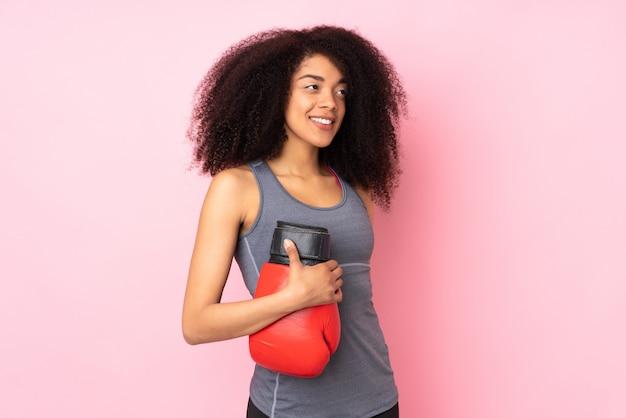 Giovane donna afroamericana di sport isolata sulla parete rosa con i guantoni da pugile