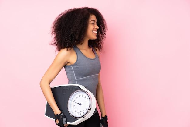 Giovane donna afroamericana di sport isolata sulla parete rosa con la pesa