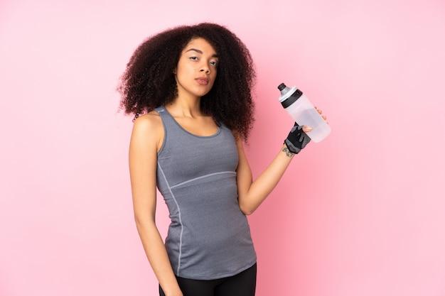 Giovane donna afroamericana di sport sulla parete rosa con la bottiglia di acqua di sport