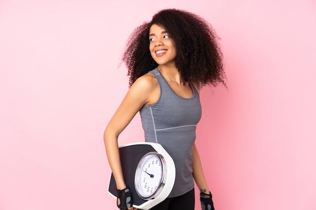 Giovane donna afroamericana di sport sulla parete rosa con la pesa