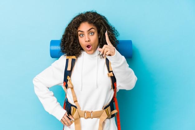 Giovane donna afroamericana di viaggiatore con zaino e sacco a pelo che ha un'idea, concetto di ispirazione.
