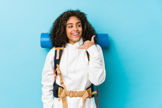 Giovane donna afroamericana di viaggiatore con zaino e sacco a pelo che mostra un gesto di chiamata di telefono cellulare con le dita.