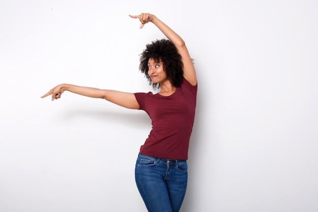 Giovane donna afroamericana felice che indica dal lato con entrambe le mani su fondo bianco