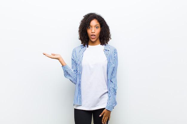Giovane donna afroamericana fresca che sembra sorpresa e colpita, con la mascella caduta tenendo un oggetto con una mano aperta sul lato