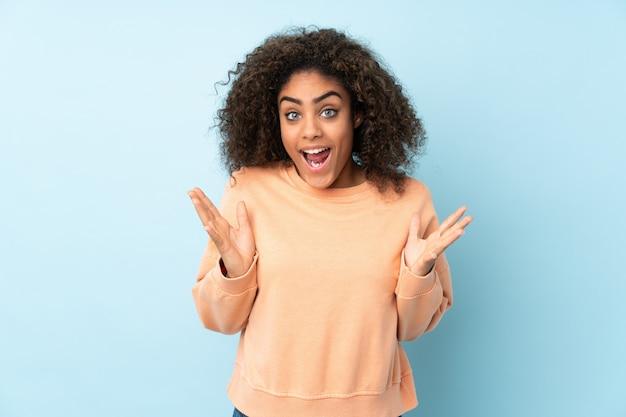 Giovane donna afroamericana isolata su spazio blu con espressione facciale di sorpresa