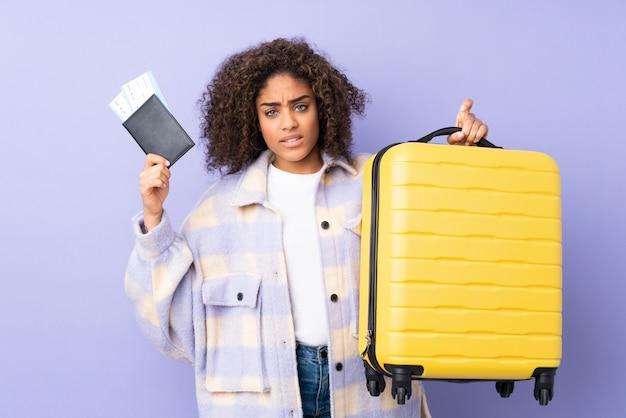 Giovane donna afroamericana isolata su viola infelice in vacanza con la valigia e il passaporto