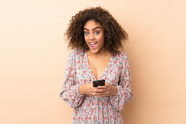 Giovane donna afroamericana isolata sul beige sorpresa e che invia un messaggio