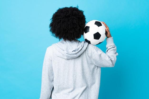 Giovane donna afroamericana isolata sul blu con pallone da calcio