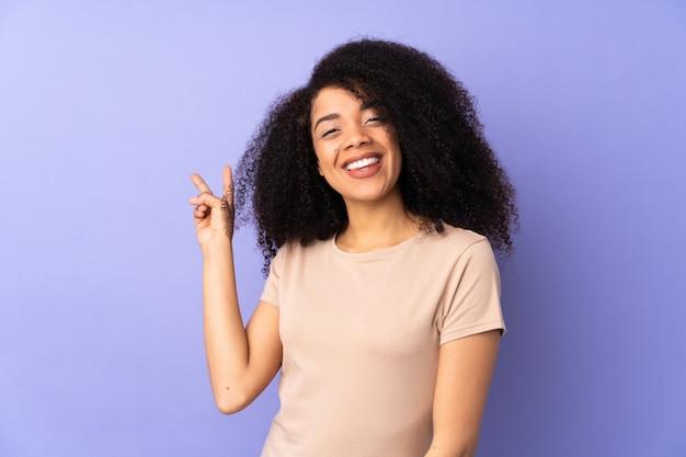 Giovane donna afroamericana isolata sul porpora che sorride e che mostra il segno di vittoria