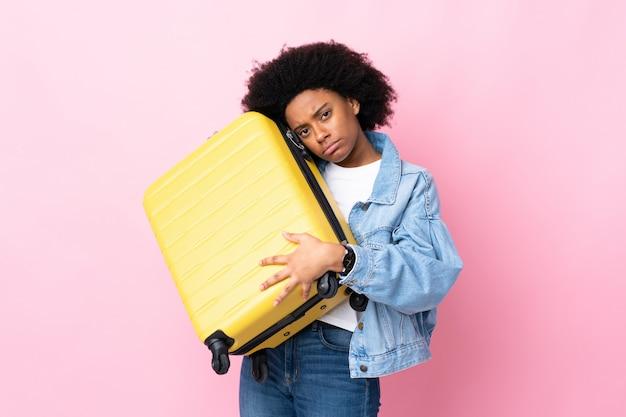 Giovane donna afroamericana isolata sul rosa in vacanza con la valigia di viaggio e infelice