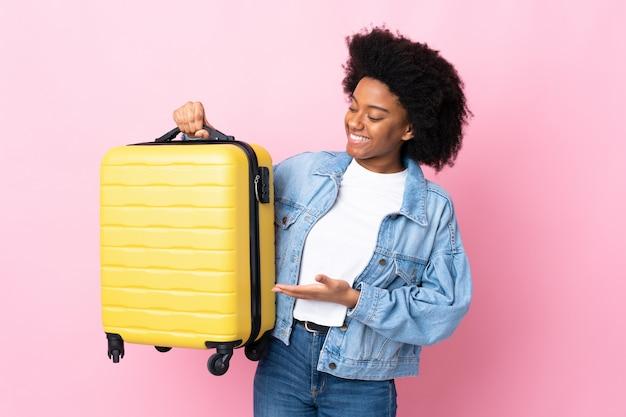 Giovane donna afroamericana isolata sul rosa in vacanza con la valigia di viaggio