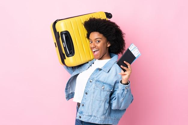 Giovane donna afroamericana isolata sul rosa in vacanza con la valigia e il passaporto