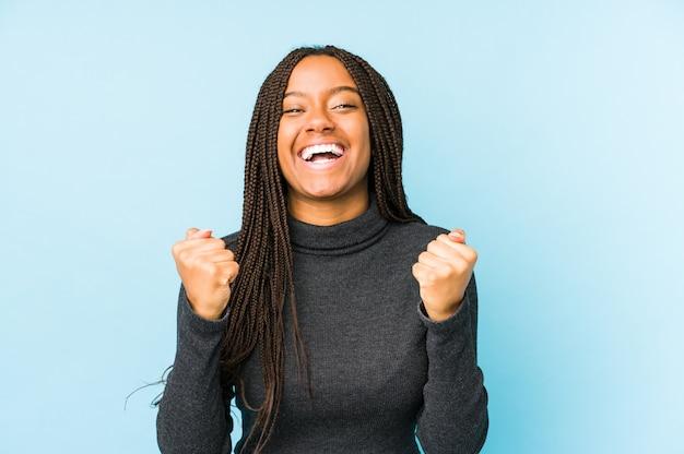 Giovane donna afroamericana isolata sulla parete blu che incoraggia spensierata ed eccitata. concetto di vittoria.