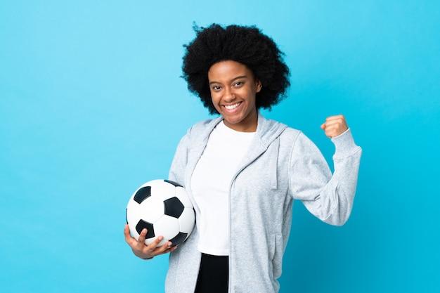 Giovane donna afroamericana isolata sulla parete blu con pallone da calcio che celebra una vittoria