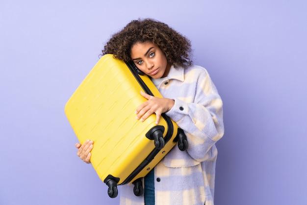 Giovane donna afroamericana isolata sulla porpora in vacanza con la valigia di viaggio e infelice