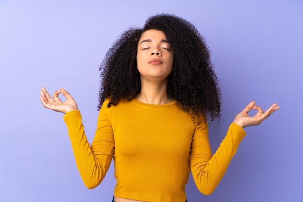 Giovane donna afroamericana isolata sulla porpora nella posa di zen
