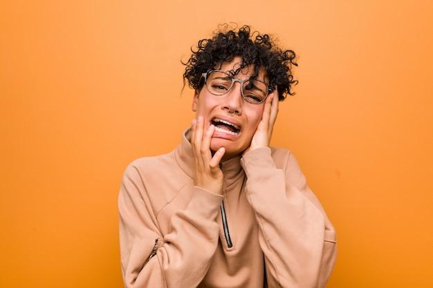 Giovane donna afroamericana mista contro una parete marrone che geme e piange sconsolata.