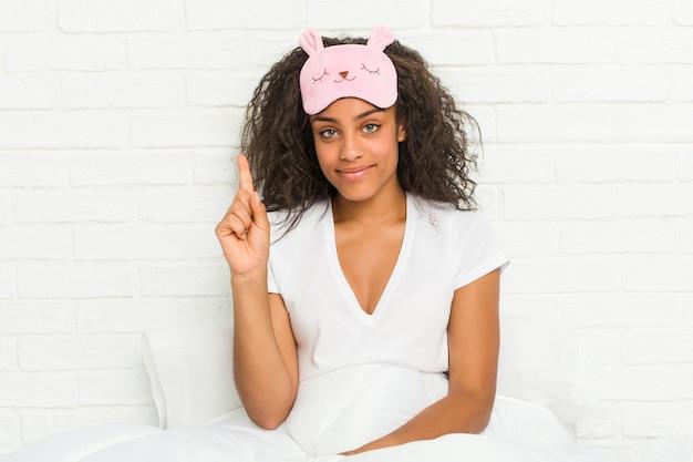 Giovane donna afroamericana seduta sul letto che indossa una maschera per dormire che mostra il numero uno con il dito.