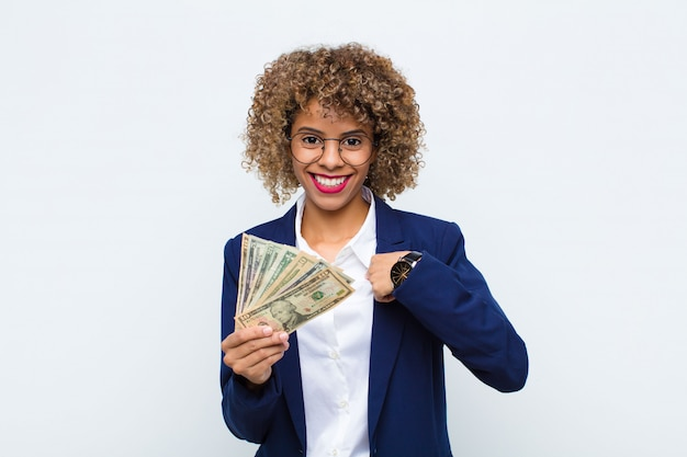 Giovane donna afroamericana sentirsi felice, sorpresa e orgogliosa, indicando se stessa con uno sguardo eccitato e stupito con le banconote in euro