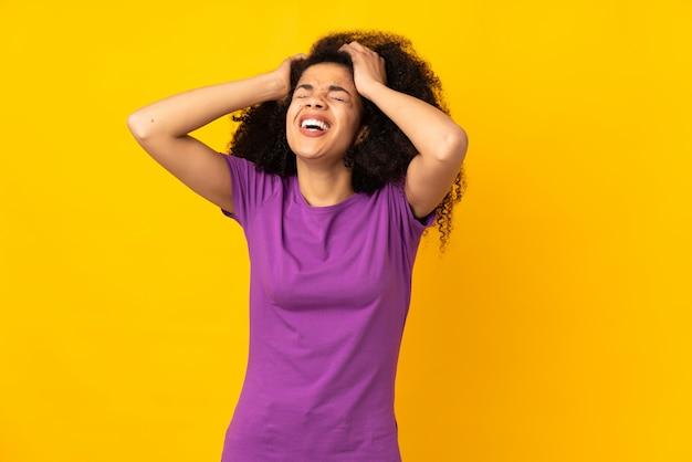 Giovane donna afroamericana sopra la parete sollecitata