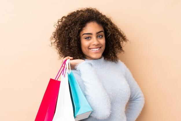 Giovane donna afroamericana sui sacchetti della spesa e sul sorridere beige della tenuta della parete